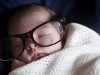 portrait of newborn baby wearing mother's spectacles
